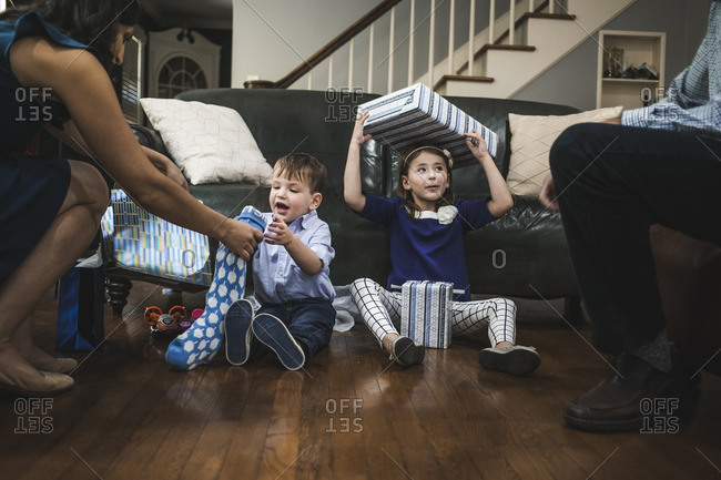 Family in a living room opening Hanukkah presents