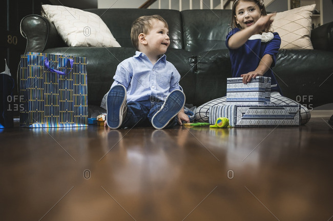 Boy and girl sitting on a living room floor opening gifts for Hanukkah