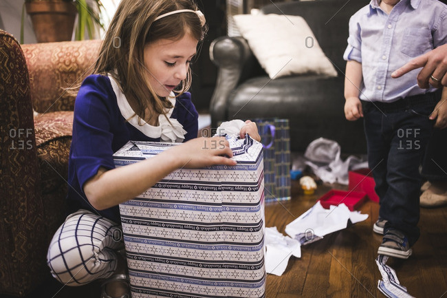 Little girl opening a wrapped present for Hanukkah