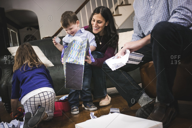 Parents helping their children open gifts for Hanukkah