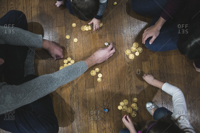 Family of four playing dreidel on a wooden floor