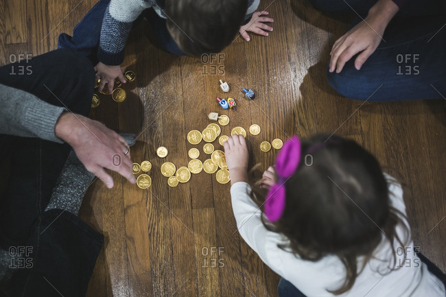 Family sitting on a wooden floor playing dreidel