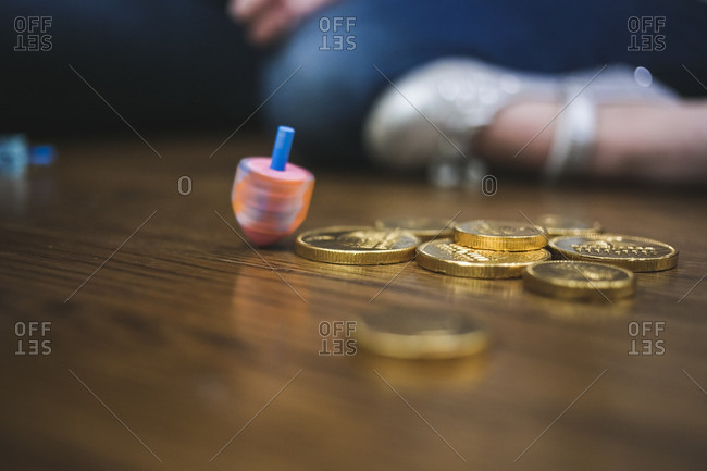Spinning dreidel on a wooden floor next to coins
