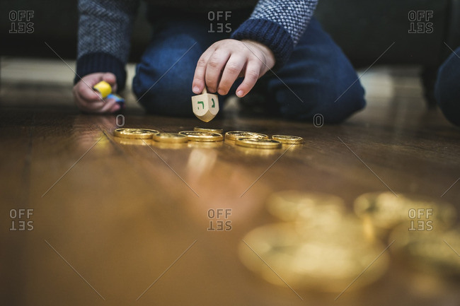 Hand of a boy preparing to spin a dreidel on a wooden floor