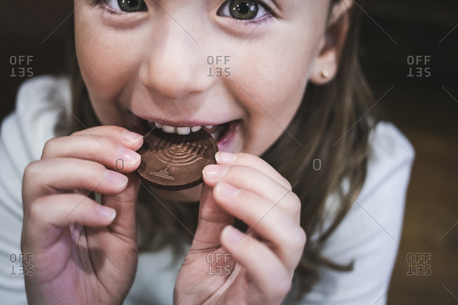 Little girl biting into a chocolate gelt coin
