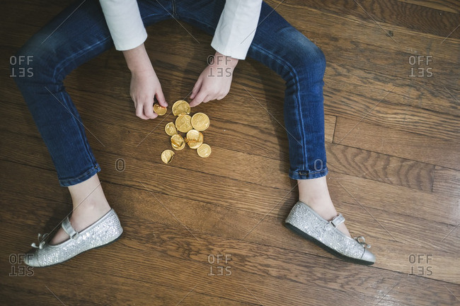 Little girl sitting on a floor with a pile of chocolate gelt coins