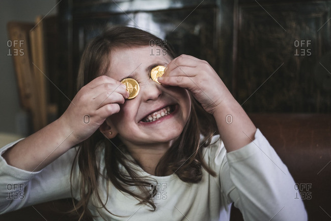 Little girl holding chocolate gelt coins over her eyes