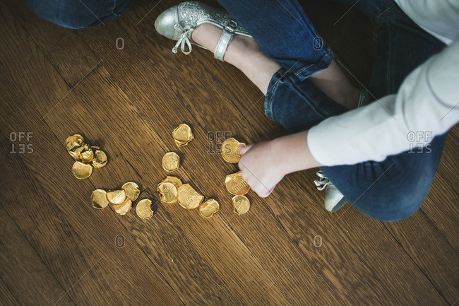 Little girl sitting on a floor with wrappers from many chocolate gelt coins