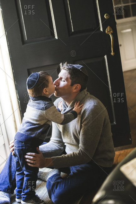 Father and toddler son in yarmulkes kissing