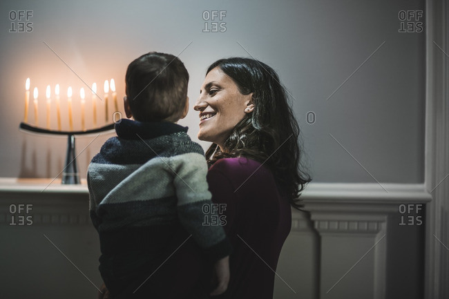 Mother and son admiring a menorah on a mantle