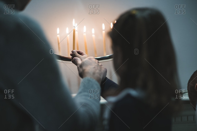 Father helping his daughter light a menorah