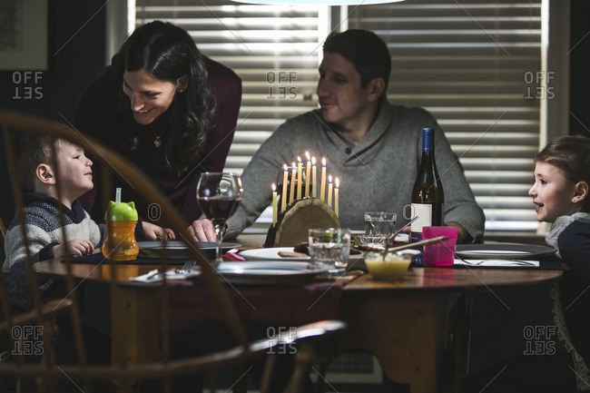 Family at a dining table with a lighted menorah