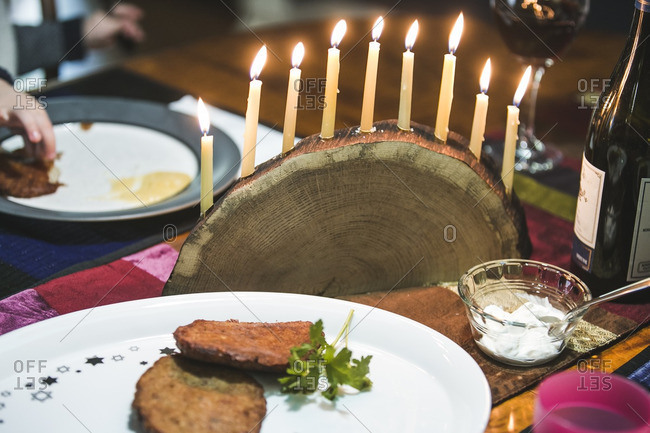Platter of latkes and a lighted menorah on a dining table