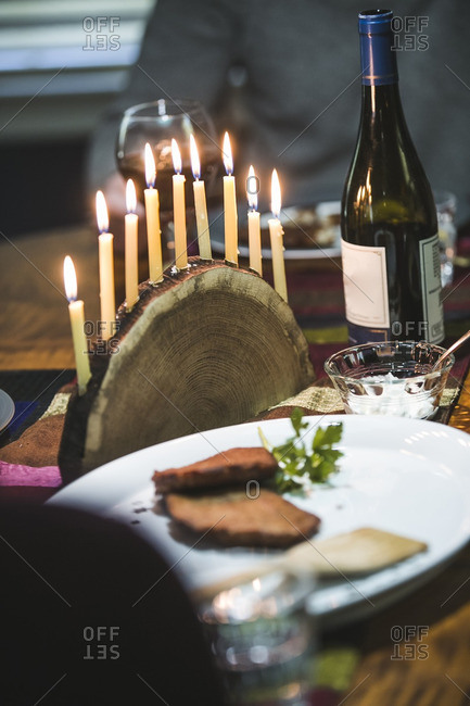 Lighted menorah and a platter of latkes on a dining table