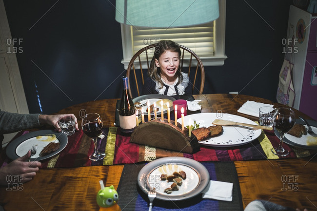 Little girl at a dining table with latkes and a menorah