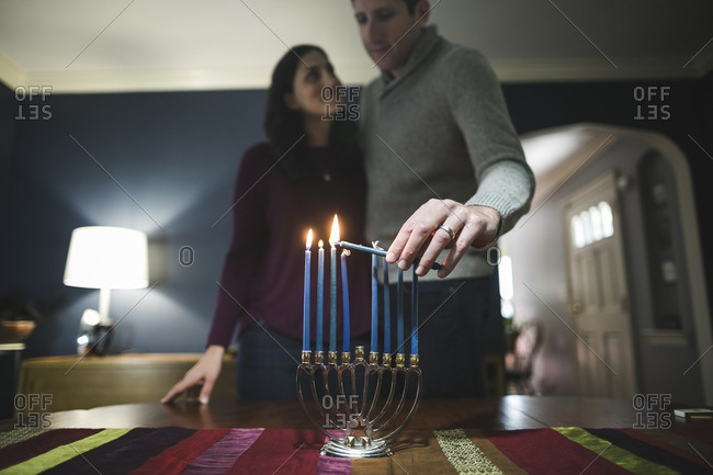 Couple lighting a small menorah on a table