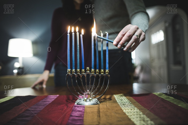 Man standing with his wife lighting a small menorah