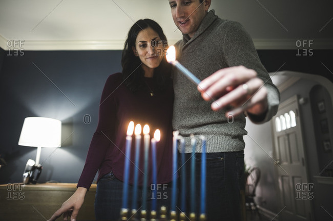 Husband and wife lighting a small menorah on a table