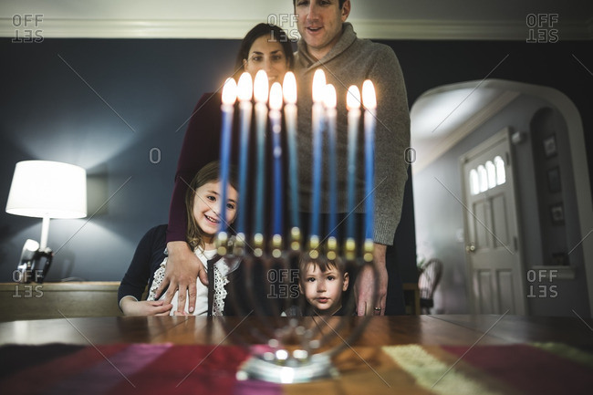Family of four standing together looking at a lighted menorah