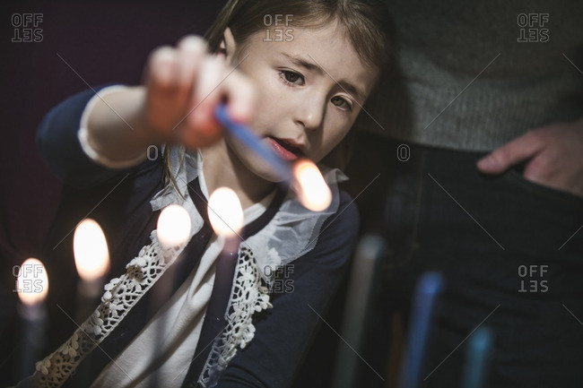 Little girl standing next to her father lighting a menorah