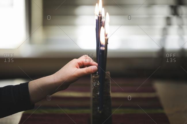 Hand of a little girl lighting a menorah
