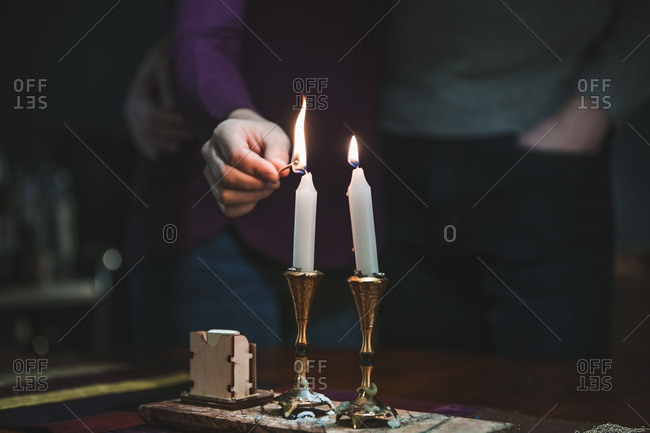 Husband and  wife lighting candles in observance of Hanukkah