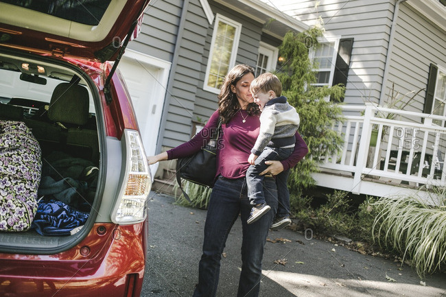 Woman holding her son and opening a car door