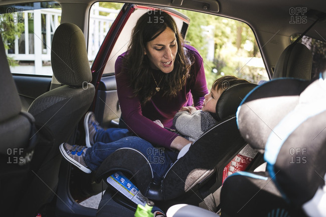 Woman putting her son in a car seat