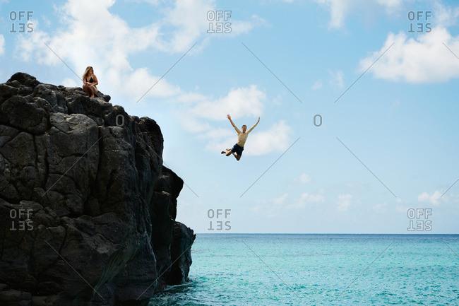 Woman watches man jump off rock into ocean