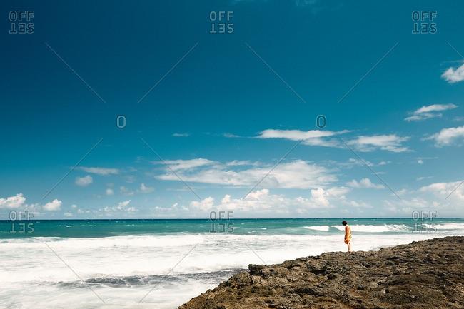 Woman in orange dress looking over cliff on ocean