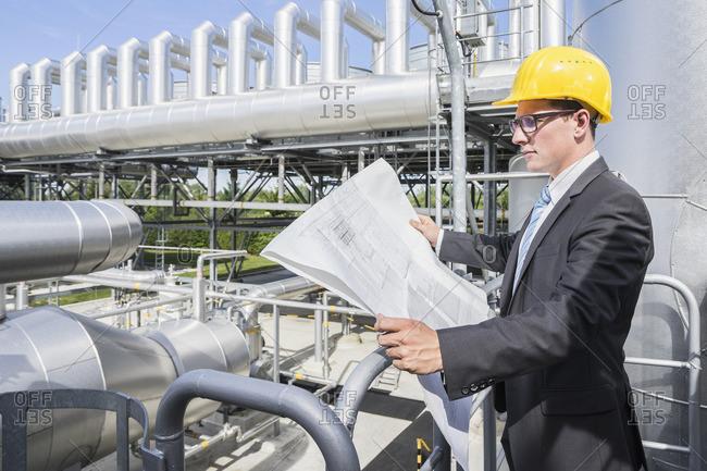 Female engineer examining blueprint at geothermal power