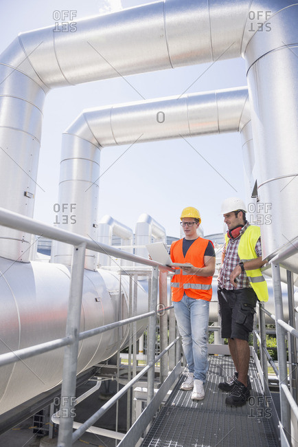 Engineer and worker in meeting with construction plan on the area of a geothermal power station, Bavaria, Germany