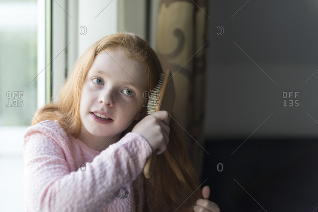 A little girl brushing her red hair.