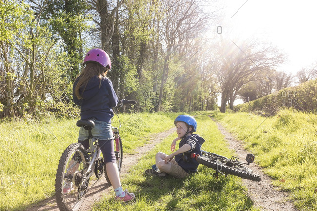 A boy and girl exploring the countryside on their bikes.