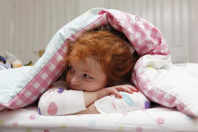 Little girl awake in bed.