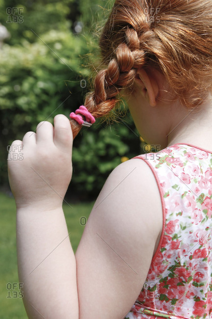 Four year old girl in her garden with plaits. View from behind.