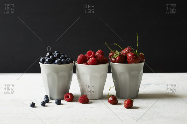 Still life of cups of berries with berries scattered on table