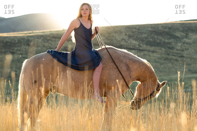 Portrait of young woman in dress on horseback