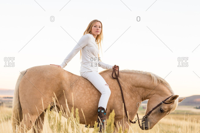 Portrait of young woman in white on her horse