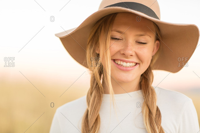 Portrait of smiling young woman in braids with floppy hat