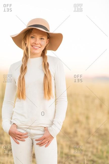 Portrait of beautiful young woman wearing a floppy hat in field