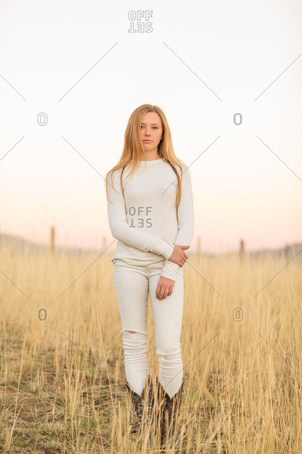 Beautiful young woman standing in field at dusk
