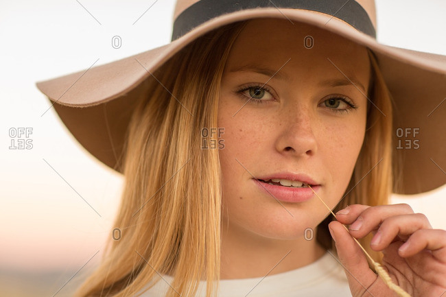 Close up of beautiful young woman in hat with piece of straw in teeth