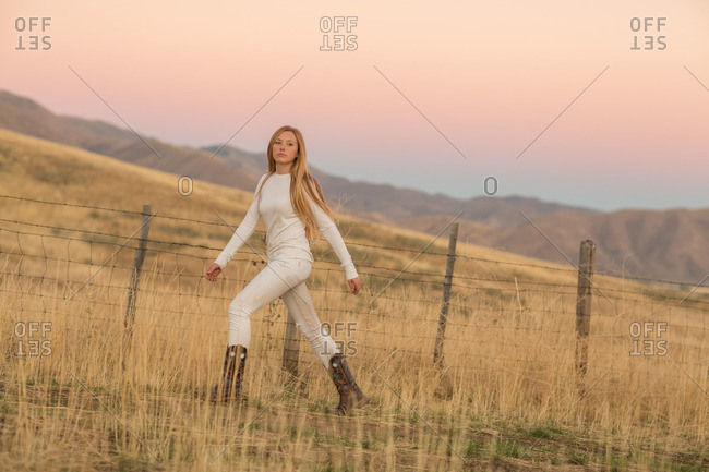 Young woman in cowboy boots walking past barbed-wire fence in field at dusk
