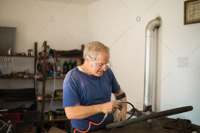 Man inflating bike tire in his workshop