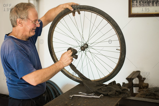 Man cleaning spokes on a bike tire with a rag