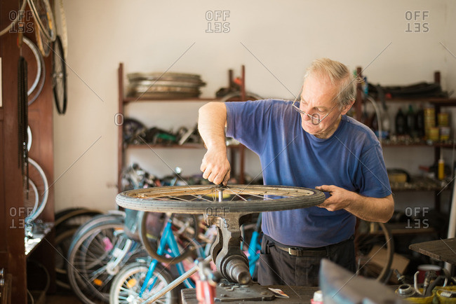 Man tightening bolt on a bike tire with a bench vise