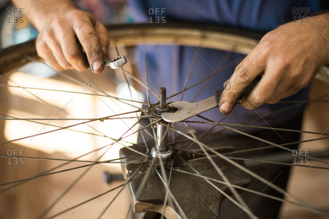 Man tightening bolt on a bike tire