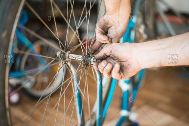 Man putting bike tire onto a bike frame