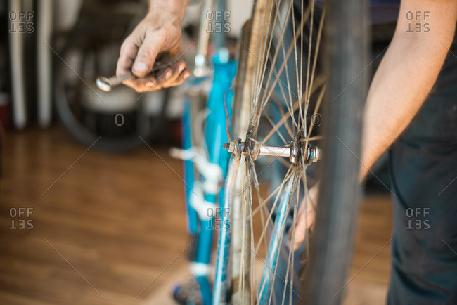 Man putting bike tire onto a bike frame in his workshop